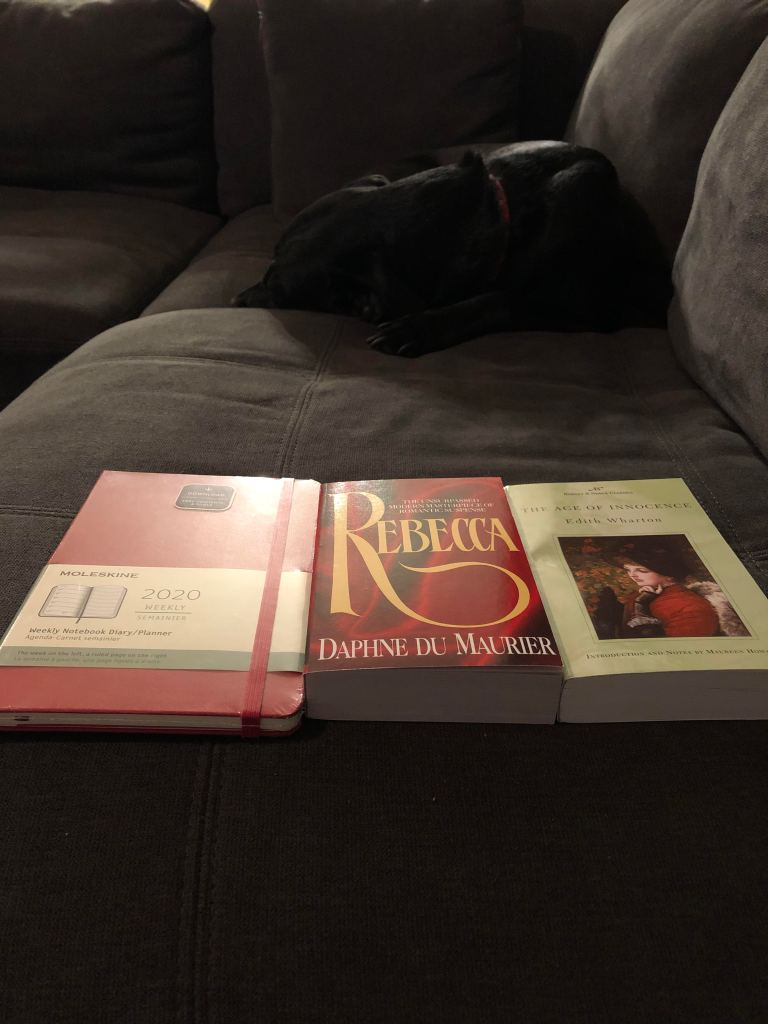 A red Moleskine 2020 weekly planner, paperback of Rebecca by Daphne Du Maurier, paperback of The Age of Innocence by Edith Wharton on cushion with a black dog lying curled up in the background.